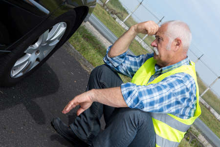 dismayed: discouraged retired man unable to change car tyre Stock Photo