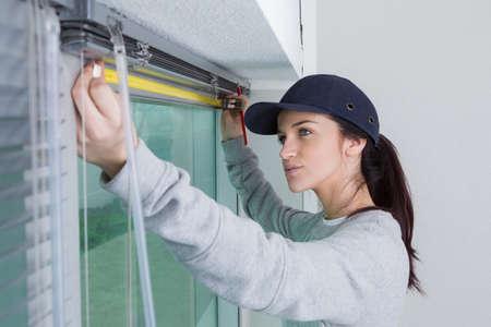 Woman measuring for window blinds Standard-Bild