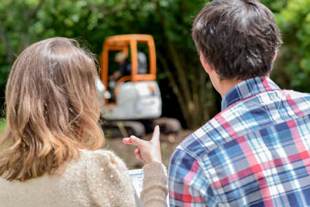 facing away: Couple pointing at working digger Stock Photo