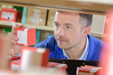 stock clerk reading the label Stock Photo