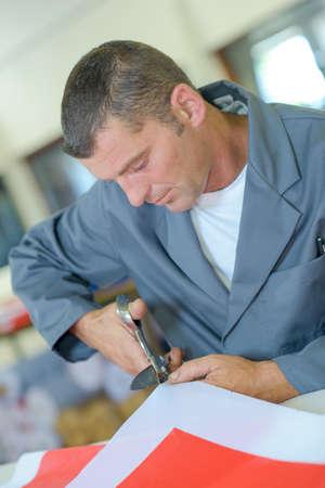 Male worker cutting fabric Stock Photo