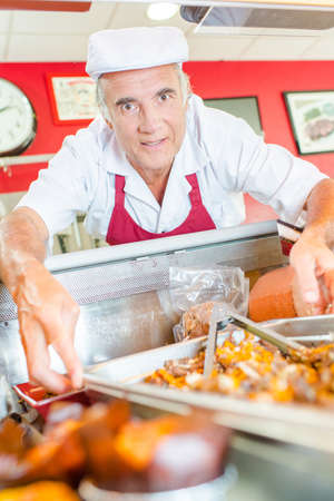 serf: Man reaching for tray of food Stock Photo