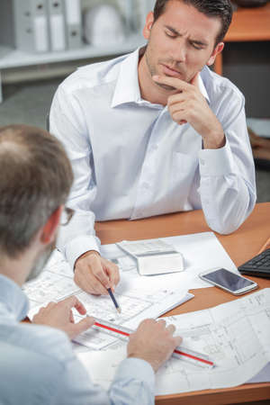Man discussing blueprints, frowning