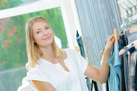 retail therapy: Lady holding top in clothes shop Stock Photo