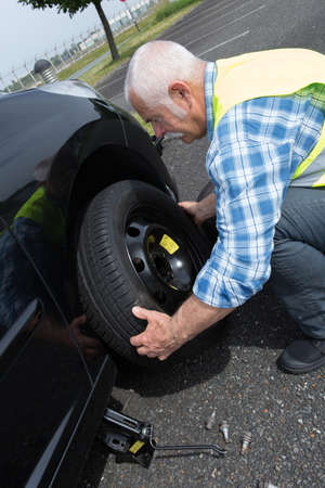 dauntless: aged man changing leaking tire on the verge