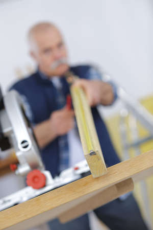 skillful: senior male carpenter using table saw for cutting wood Stock Photo