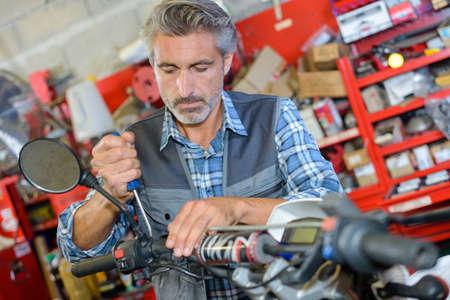 dismantle: Mechanic working on handlebars of scooter