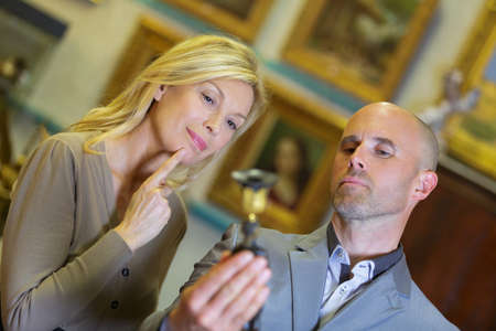 bidder: man and woman examinating an object at auction site Stock Photo