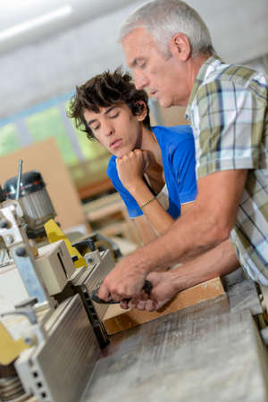 miter: Two carpenters gathered by a machine Stock Photo