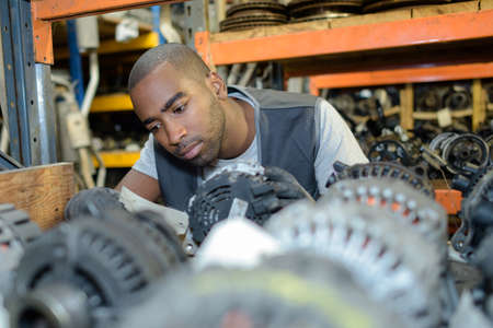 dismantled: Man looking through parts in scrap yard Stock Photo