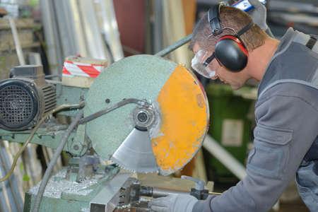 worker cutting through metal rod