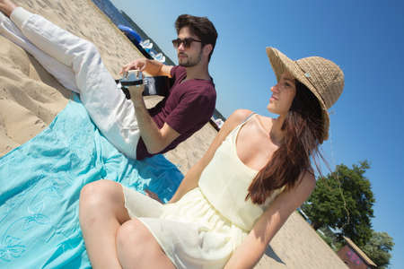 serenading: young man with his guitar and girlfriend on the beach