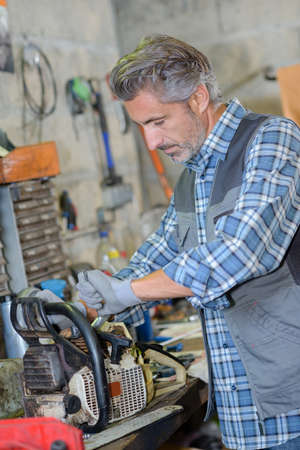 mechanic fixing a chainsaw