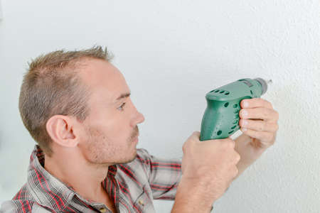 pierce: Builder drilling hole in wall Stock Photo