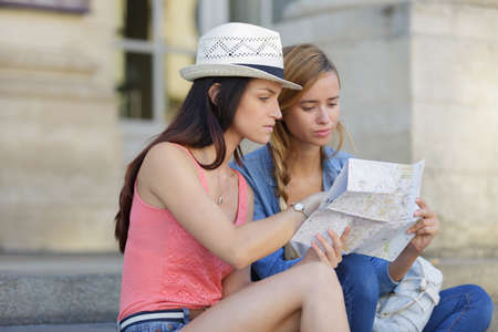 explores: lost and confused girl friends looking for directions on map