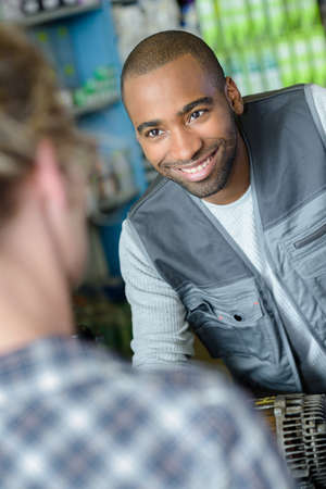 smiling mechanic talks to customer about car part Stock Photo