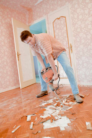 white work: Man demolishing a floor