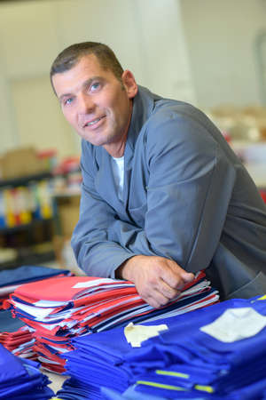 Man leaning on piles of fabric