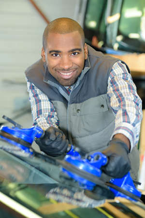Man fitting new windscreen in vehicle Stock Photo