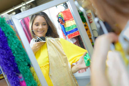 Lady holding colorful costume to mirror Stock Photo