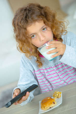 brunett: girl holding glass of milk and remote control Stock Photo