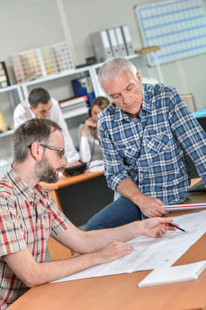 Two men discussing paperwork, one sitting on desk