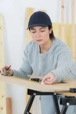 architect tools: portrait of happy female woodworker drafting new project at workshop Stock Photo