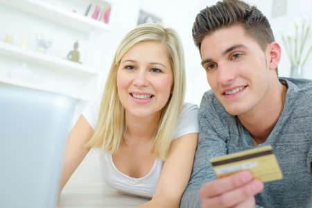 Couple using computer holding a credit card