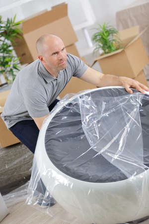 furniture home: male mover carrying sofa