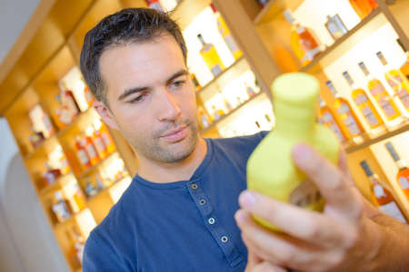 concerned male customer looking at label jar in food store