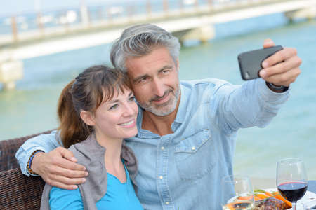 vacationer: taking selfie during a meal