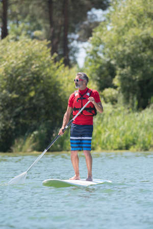 paddles: man enjoying a ride on the lake with paddleboard Stock Photo