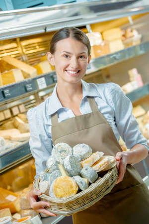 food supply: Shop assistant holding basket of cheeses Stock Photo