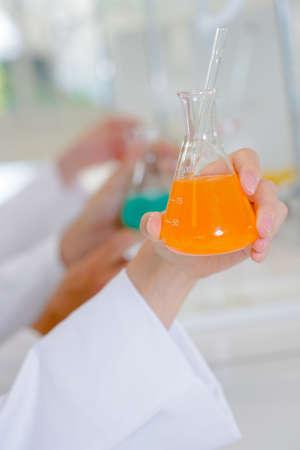 stirrer: Female hand holding flask containing orange liquid