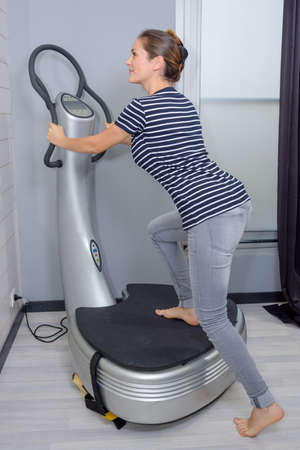 woman getting on vibrating platform fitness machine