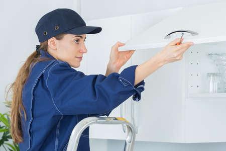 handywoman: fitting a kitchen Stock Photo