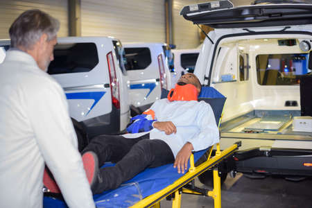 paciente en camilla: docter taking patient out of ambulance on a stretcher