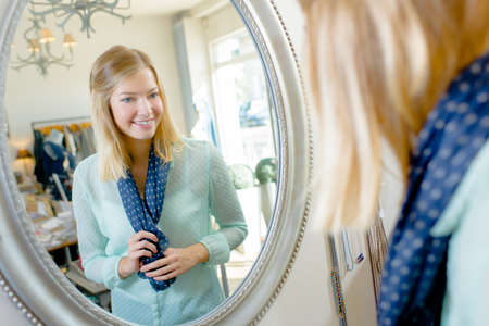 reflection in mirror: Woman looking her reflection in a mirror Stock Photo