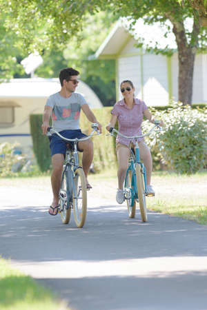 static bike: Couple cycling through campsite Stock Photo