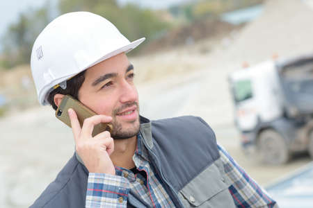 Man on cellphone on construction site