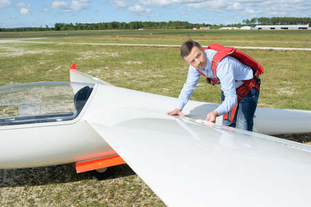 Pilot looking at wing of sailplane