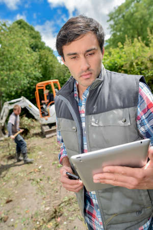 ongoing: man outdoors holding tablet