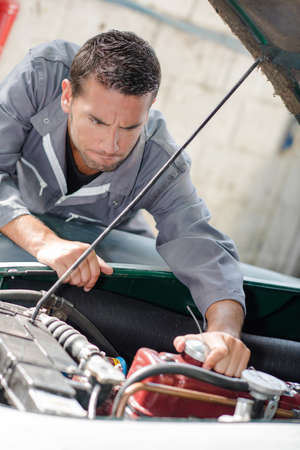 replenish: Man trying to fix his car