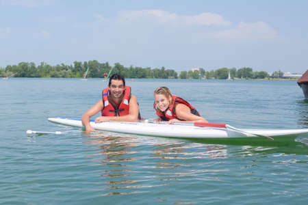 young couple swiming with paddle board in a lake