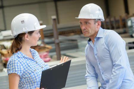 animosity: Conversing man and woman wearing hardhats