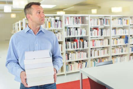 factual: man carrying a pile of books