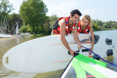 attaching: Couple attaching sail to windsurfing board