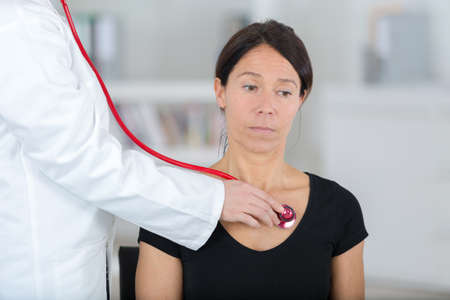 female doctor examining the patient with stethoscope Stock Photo