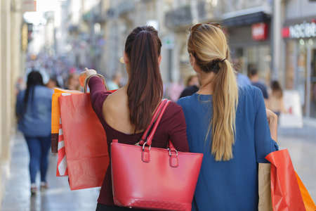overspending: young happy and wealthy women shopping