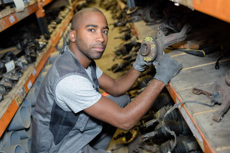 salvage yards: Man with stock of second hand car parts Stock Photo